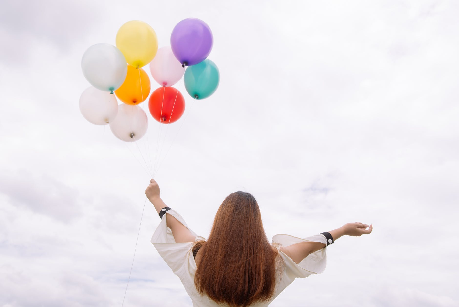 worm s eye view of woman holding balloons